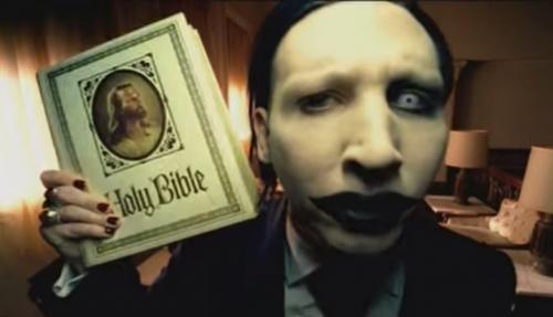 """Marilyn Manson, qui con la Bibbia (il libro dei libri) in una scena del video di """"Beat the Devil"""". Sta per arrivare il suo nuovo disco, """"THE PALE EMPEROR"""""""