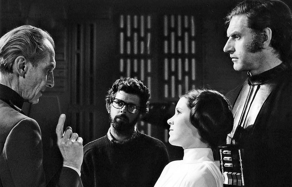 Peter Cushing, David Prowse e Carrie Fisher insieme al regista George Lucas sul set del primo film della daga di Star Wars, 'Una Nuova Speranza'