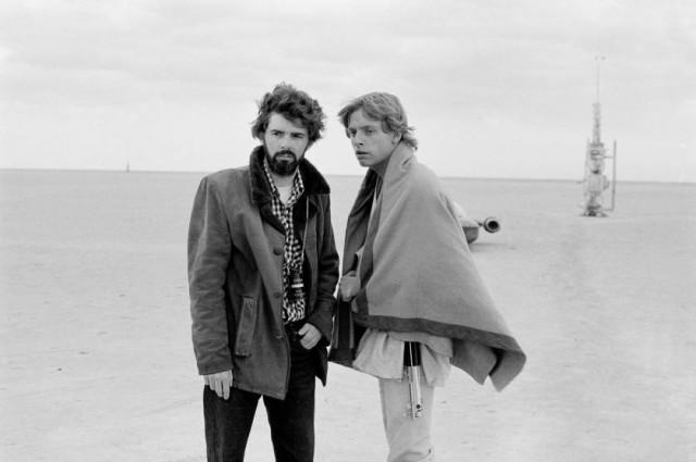 Due giovani George Lucas e Mark Hamill discutono sul set di Star Wars. Alle loro spalle si intravede il landspeeder X-34, la celebre utilitaria a repulsione di Luke Skywalker