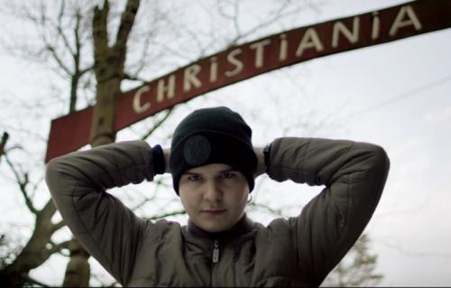 """Lukas Graham posa davanti all'ingresso del quartiere di Copenhagen dove è nato, """"Christiania"""""""