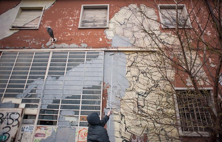 Blu mentre cancella i suoi graffiti a Bologna. Foto: Giap