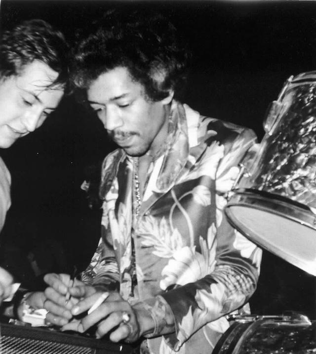 La foto scattata da Fabio Treves a Jimi Hendrix che firma un autografo a un fan al Piper di Milano nel 1968
