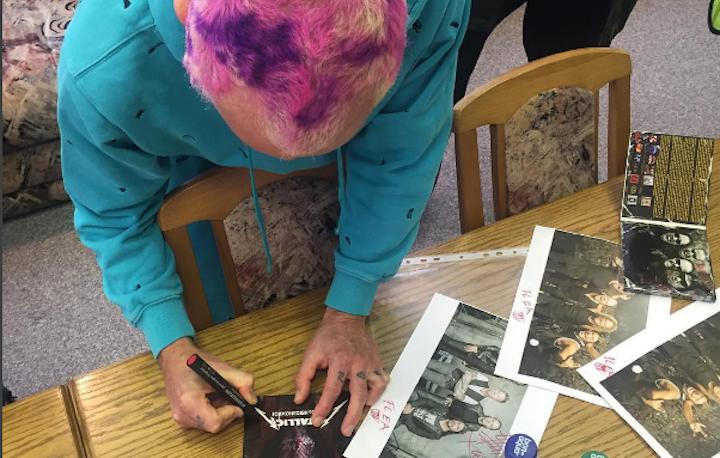 Flea firma autografi su foto dei Metallica, come richiesto dalla polizia bielorussa