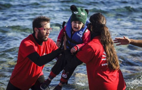 Alcuni volontari a Lesbo aiutano una bambina che ha attraversato in nave l'Egeo dalla Turchia. Foto UNHCR/Achilleas Zavallis