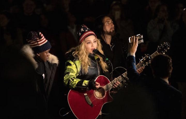 Berretto, microfono e chitarra: Madonna improvvisa un concerto in strada pro Hillary
