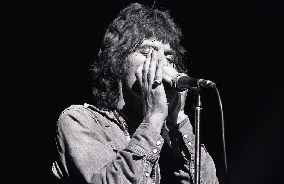 Mick suona l'armonica durante una performance negli anni '70  (Photo by Robert Knight Archive/Redferns)
