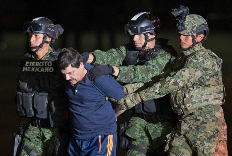 """Mexican army soldiers escort drug lord Joaquin """"El Chapo"""" Guzman to a helicopter to be transported to a maximum security prison at Mexico's Attorney General's hangar, in Mexico City, Friday, Jan. 8, 2016. The world's most-wanted drug lord was captured for a third time in a daring raid by Mexican marines, six months after he tunneled out of a maximum security prison in a escape that embarrassed the government and strained ties with the United States. (AP Photo/Eduardo Verdugo)"""