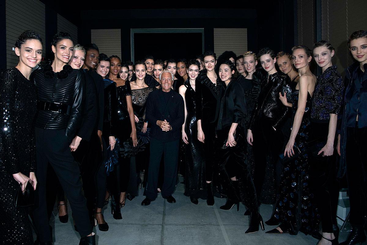 Giorgio Armani posa con le sue modelle al termine della sfilata milanese AI 2019-2020